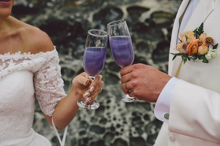Luminous purple toasting drinks for a celestial themed beach wedding designed by Victoria BC wedding stylist Party Mood.