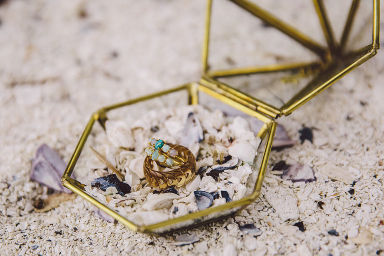 Bride and groom wedding rings in a geometric glass and brass box on the beach for a seaside wedding celebration styled by Party Mood.