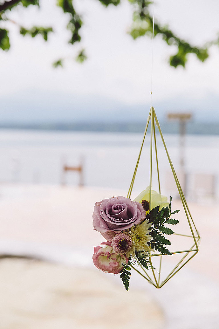 A metal geometric hanging floral fixture enclosing wedding florals designed for a modern new-age beach wedding in Victoria BC styled by wedding planner Party Mood.