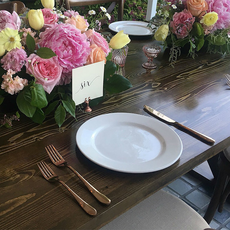 Table setting design featuring rose gold cutlery, pink glass votive holders, and pastel florals by Victoria BC wedding decor rental company Party Mood.