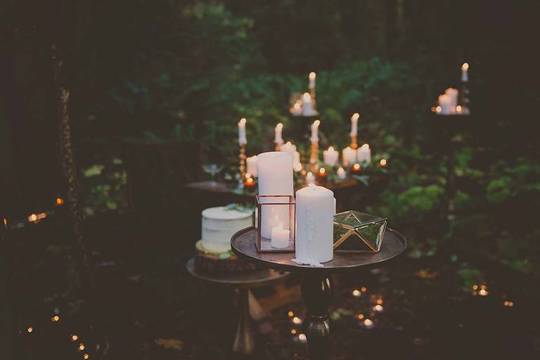 Gold accent tables, brass stands, brass candlesticks, and copper framed glass boxes create an etherial atmosphere for this woodland themed wedding.